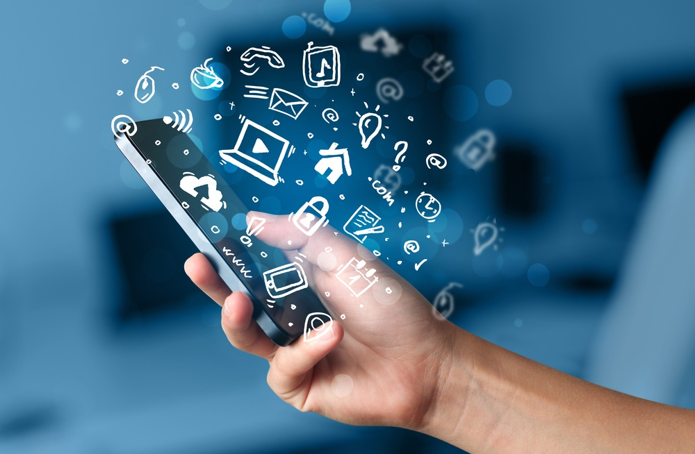 Hand holding smartphone with media icons and symbol collection.jpeg